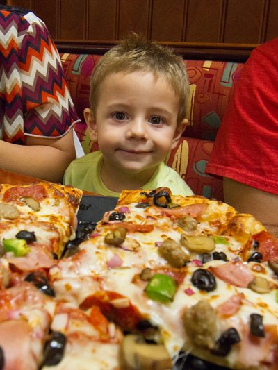 Child Eagerly Awaits Delicious Pizza